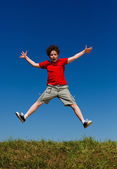 Boy jumping, running against blue sky — Stock Photo