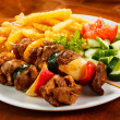 Grilled meat with French fries and vegetable salad — Stock Photo