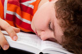 Tired kid sleeping on book — Stock Photo
