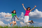 Mother and daughter jumping against blue sky — Stock Photo