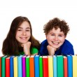 Students sitting behind pile of books — Stock Photo #33071477