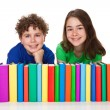 Students sitting behind pile of books — Stock Photo #33072123