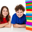 Students sitting behind pile of books — Stock Photo #33072365