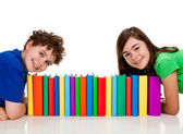 Students sitting behind pile of books — Stock Photo