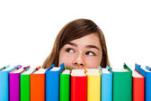 Girl peeking behind pile of books — Stock Photo