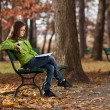 Girl reading book sitting in park — Stok fotoğraf