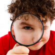 Boy looking through magnifying glass — 图库照片