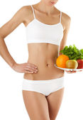 Slim woman with fruit on plate — Stock Photo