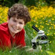 Boy using microscope outdoor — Stock Photo