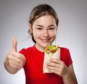 Girl eating big sandwich — Stock Photo