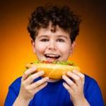 Boy eating big sandwiches — Stock Photo