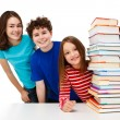Students peeking behind pile of books — Stock Photo