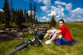 Girl and boy resting after biking — Stock Photo