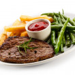 Grilled steaks, baked potatoes and vegetables — Stock Photo #33504211