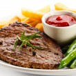 Grilled steaks, baked potatoes and vegetables — Stock Photo #33504215