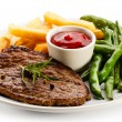 Grilled steaks, baked potatoes and vegetables — Stock Photo #33504281
