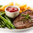 Grilled steaks, baked potatoes and vegetables — Stock Photo #33504343