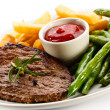 Grilled steaks, baked potatoes and vegetables — Stock Photo #33504381