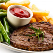 Grilled steaks, baked potatoes and vegetables — Stock Photo #33504427