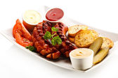 Grilled sausages, baked potatoes and vegetables — Stock Photo