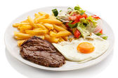 Grilled steaks, French fries, fried egg and vegetables — Stock Photo