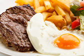 Grilled steaks, French fries, fried egg and vegetables — 图库照片