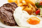 Grilled steaks, French fries, fried egg and vegetables — ストック写真