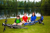 Active family resting after biking — Stock Photo