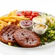 Grilled steaks, French fries and vegetables — Stockfoto