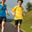 Teenage girl and boy running outdoor — Stock Photo