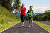 Teenage girl and boy running outdoor — Stockfoto