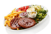 Grilled steaks, French fries and vegetables — Stock Photo