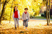 Girl and boy walking in city park — Stock Photo