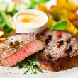 Grilled steaks, baked potatoes and vegetable salad — Stock Photo