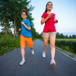 Teenage girl and boy running — Stock Photo