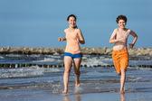 Adolescente et garçon sauter, courir sur la plage — Photo