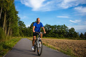 Young man riding bike — Stock Photo