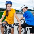 Teenage girl and boy riding bikes — Photo