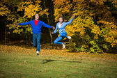 Woman and man jumping in park — Stock Photo