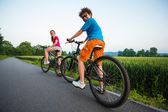 Teenage girl and boy riding bikes — Stock Photo