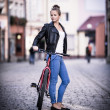 Young woman and bike in city — Stock Photo #46960763