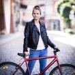 Young woman and bike in city — Stock Photo #46960831