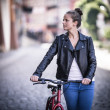 Young woman and bike in city — Stock Photo #46960917