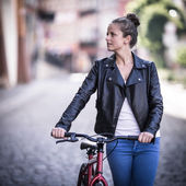 Young woman and bike in city — Stock Photo