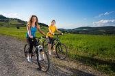 Two young women biking — Stock Photo