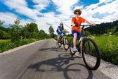 Teenage girl and boy riding bikes — Stock fotografie