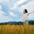 Girl holding arms up against blue sky — Stock Photo #9680156
