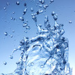 Water splash on blue background - Stock Photo