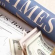 Financial newspaper with paper money and pennies — Stock Photo