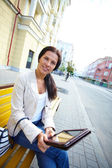 Woman with tablet on the bench — Stock Photo